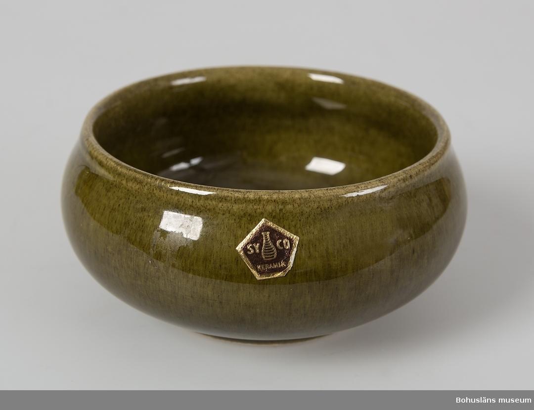 """Sockerskål av keramik glaserad i mörkt gröngult melerat med brunt inslag. Utåtbuktande sidor, vid rund öppning, mynningskanten svagt utåtböjd. Märkt på undersidan: oläsligt, SYCO, oläsligt troligen siffror. Märkt på utsidan upptill på ett ställe med en femkantig brun klisteretikett med guldfärgad bild av en vas och text: """"SYCO KERAMIK"""". En liten skada på mynningskanten (glasyren av). Hör samman med kaffekopp UM26835, assiett UM26836 och gräddkanna UM26837.  För ytterligare upplysningar se UM26835."""