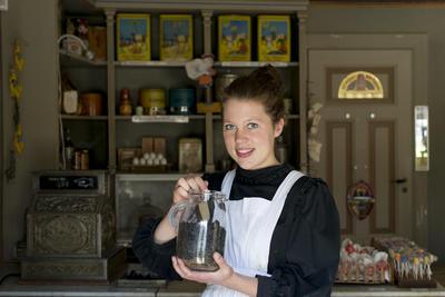 Kvinne inne i kolonialen holder sukkertøykrukke