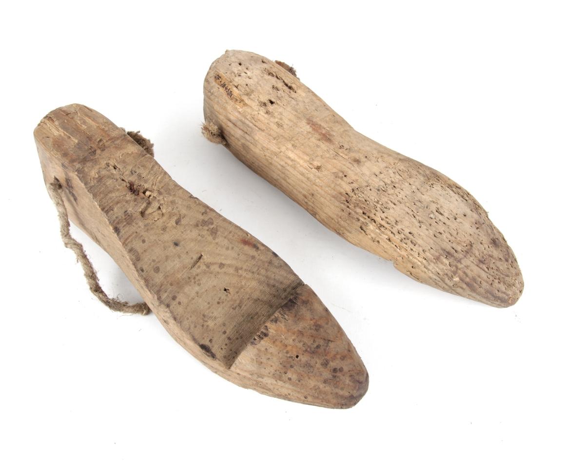 """Et par trelester. Lesten er en """"kopi"""" av foten, brukt til å skjære til og sy skotøy over, eller til å sette i ferdig skotøy for at det skal holde rett form.  Tau festet i bakre ende av hver lest."""