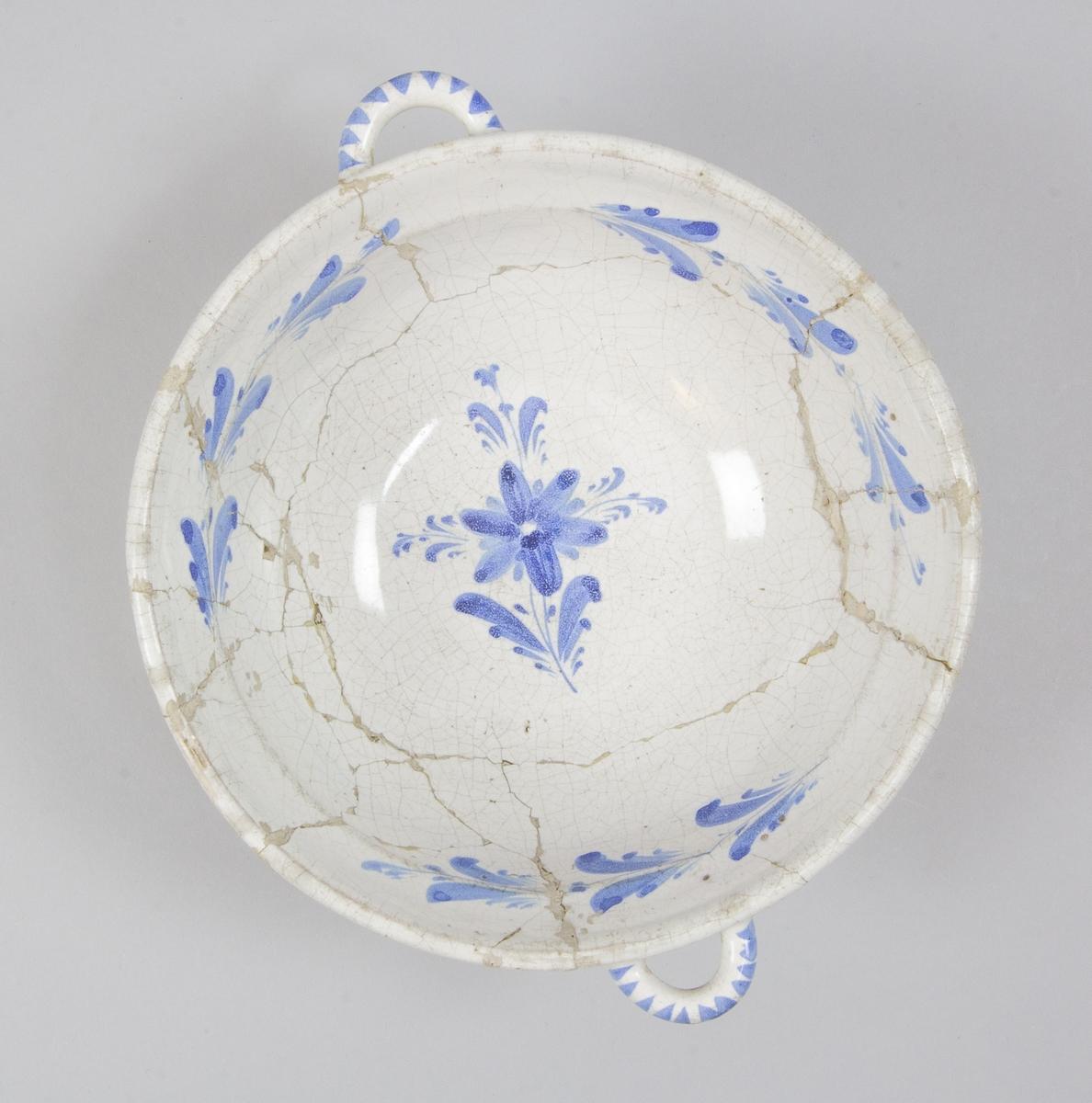 Skål av vitglaserad fajans med två horisontella öron. Invändigt målad blå dekor med en blomma med kvistar, runt mynningen en bladranka, uppdelad i tre delar. Tillverkad vid Marieberg, sannolikt under Stens period 1769-1788. Märkt med fabriken tre stiliserade kronor, MB samt målarsignatur CB.