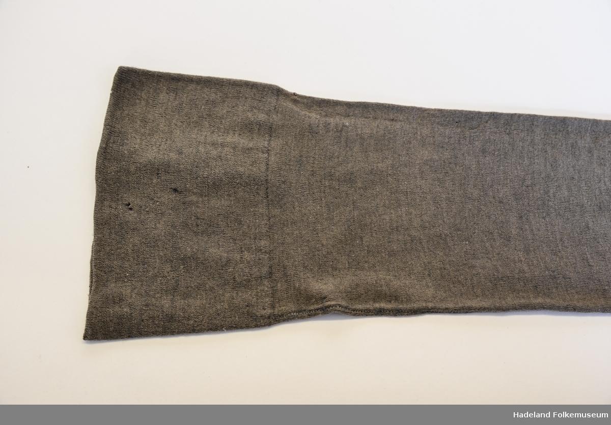 Strømper,1 par, kvinne. Grå, ull og bomull blandet. Trikotasje. Glattstrikket med 9cm dobbel kant øverst. Søm midt bak. Foten hullet og stoppet.