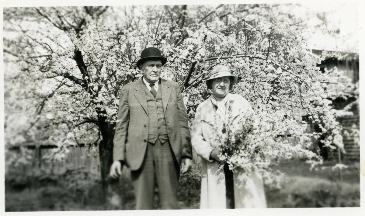 En mann og en kvinne foran et stort blomstrende tre. Kvinnen holder en bikett blomster i hendene.