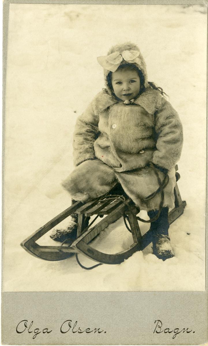 En liten pike avbildet sittende på en kjelke. Jenta er iført varm vinterjakke og lue med sløyfe på.