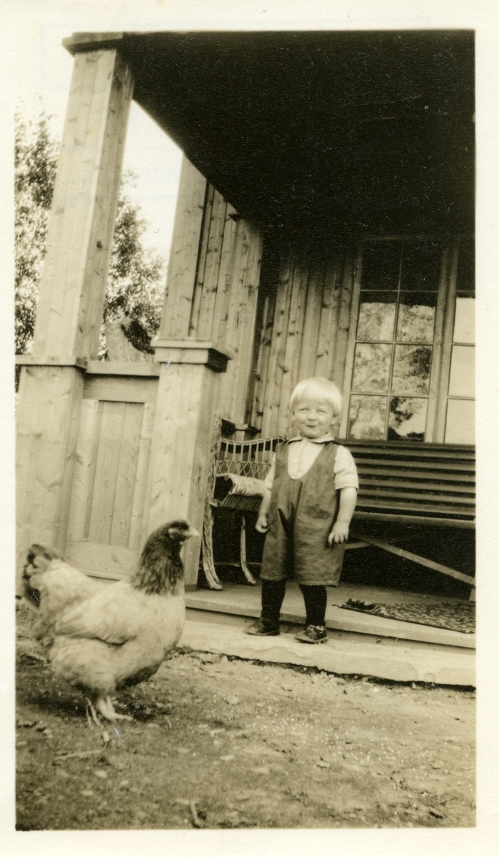 En liten gutt står ved et hus. Foran ham er det en høne. Gutten er ikledd kortbukse med strømper og en lys trøye.