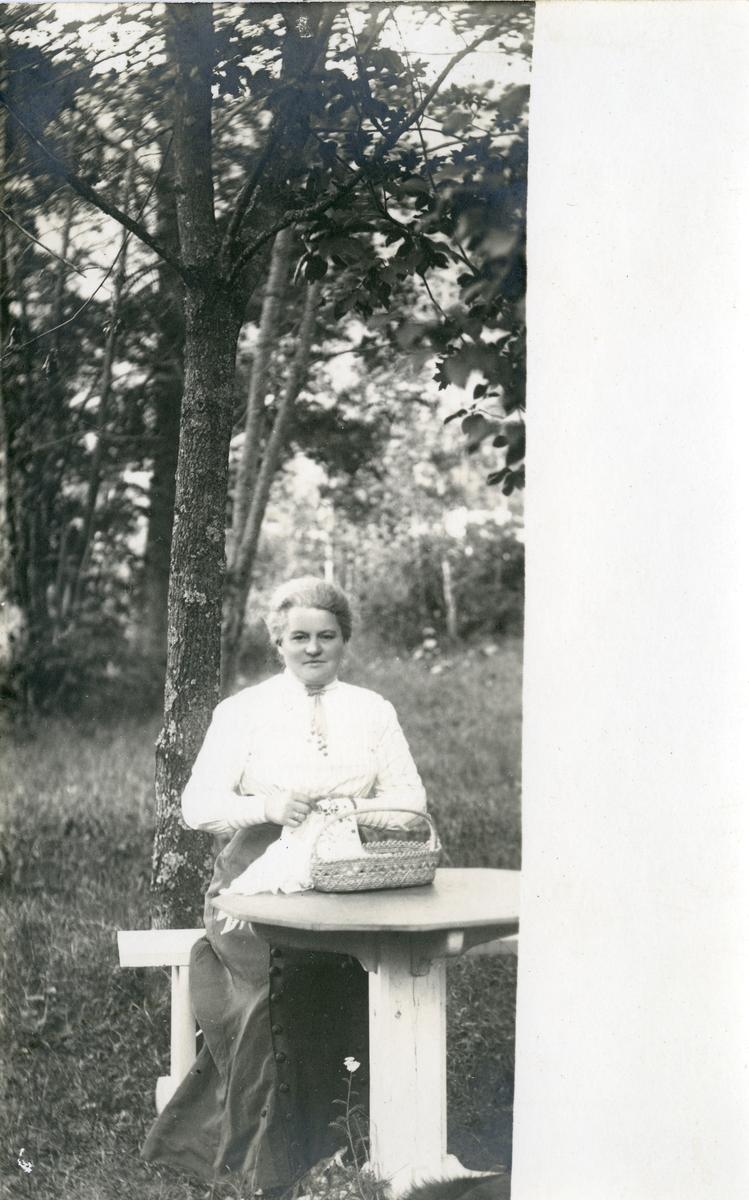 Marie Høyer sitter ved et bord i en hage. Hun holder sysaker i hendene.