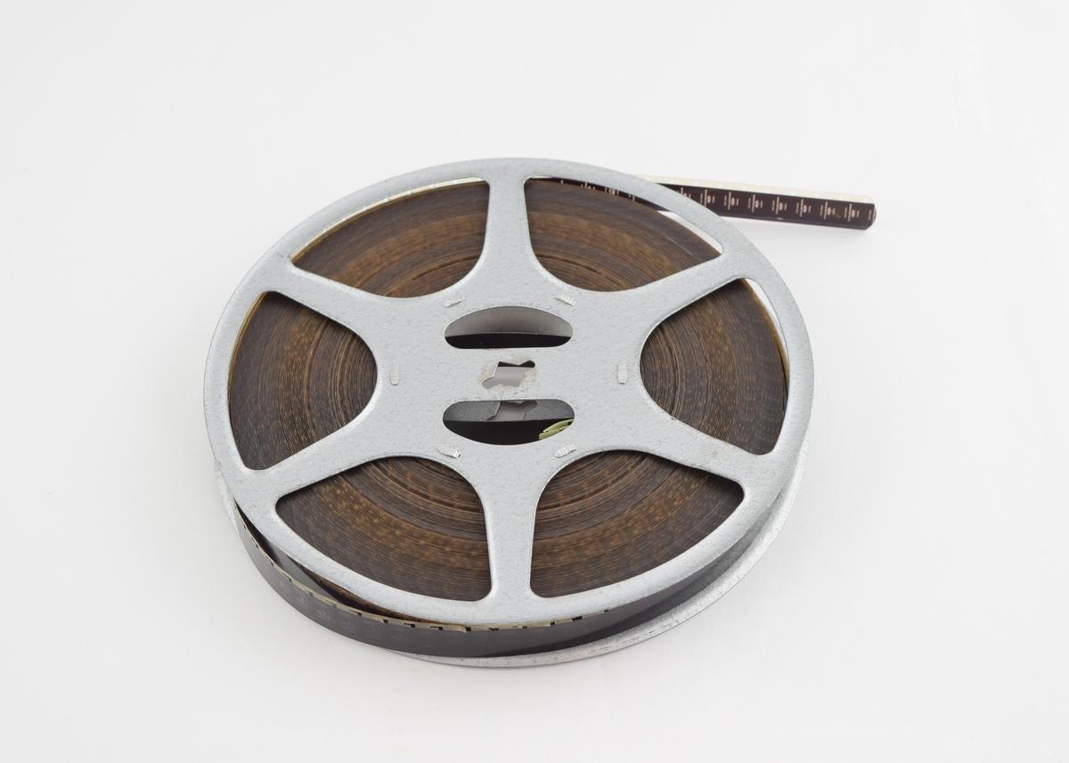 Filmrull i eske. Film på metallspole. Firkantet papir etui åpnes langs en av sidekantene. Lærreim med trykkknapp.