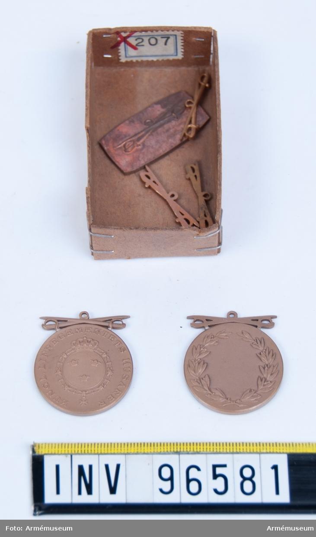 Två medaljer i brons utan medaljband och fyra delar till medaljer för Livregementets husarer. Förvaras i en ask.