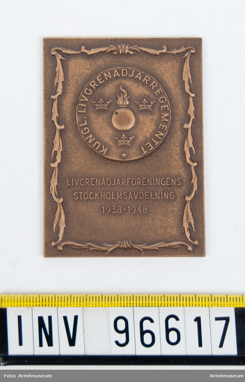 Plakett i brons för Livgrenadjärföreningens Stockholmsavdelning, Stockholm. Stans nr 20131. Med slinga nr 963 samt punsad medalj Kungl. Livgrenadjärregementet, granat, 3 kronor samt text och 5-uddig stjärna. Under medaljen inskr. LIVGRENADJÄRFÖRENINGENS STOCKHOLMSAVDELNING 1938-1948. Stansen härdad den 29 oktober 1948.