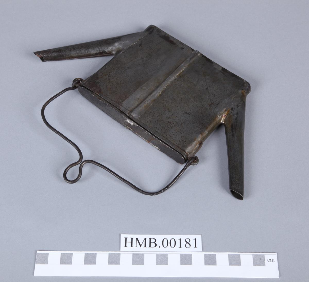 Flat, firkantet. Gjenstanden har lokk, tut i begge ender og hank til oppheng. Se HMB.00182-HMB.00192.