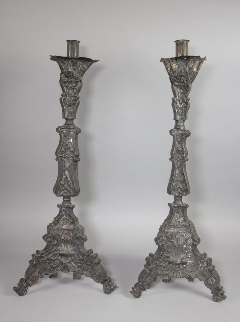 Ljusstakar, 1 par, troligen tillverkad av nysilver, starkt oxiderat. Pressad dekor med rocailler och växtornamentik. Tre fötter. Ljuspipa, cylindrisk, och droppskål.