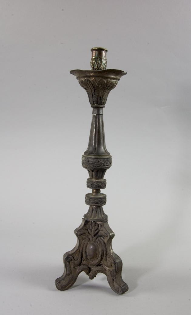 Ljusstake tillverkade av metall, troligen starkt oxiderat nysilver, på tre profilerade fötter. Droppskål. Ljuspipa av mässing. Gjuten och pressad dekor med palmetter, blombårder och kartuscher inom bandstavslingor.