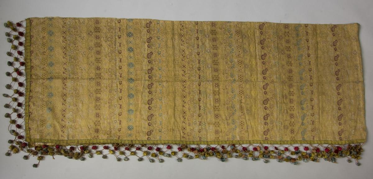 Skynke av mönstervävt sidentyg i lila, ljusblått, turkos, grönt med flera färger. Geomtriska former och blomslingor. På tre sidor bandkantat med bollfrans. Skynket hopsytt av två bitar.