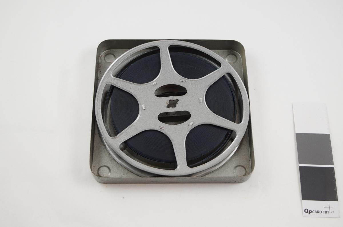 Filmrull i eske. Film på metallspole. Kvadratisk metalletui med avrundede hjørner, to løse deler: bunn og lokk.