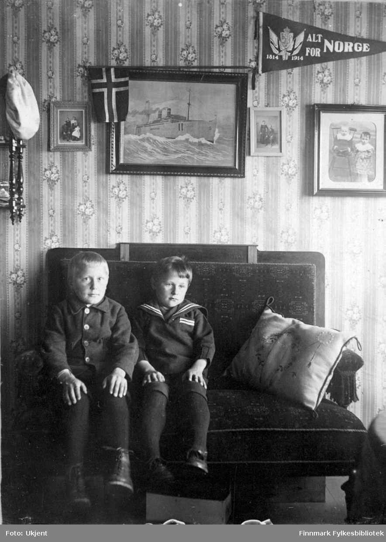 Peder Mathisen jr. og Anton Mathisen sitter på en sofa i en stue. Peder er kledd i jakke, knebukser og sko. Anton har på seg en maritim - inspirert skjorte. På sofaen ligger det en dekorativ pute. Under sofaen kan man se at det ligger en kasse av noe slag. På veggen kan man se portretter av andre mennesker, et maleri, et norskeflagg og en vimpel det står 'alt for Norge, 1814-1914' på. Veggen har en vakker blomsstrete tapet. Man kan se at det henger en hatt på en hylle ved siden av Peder.