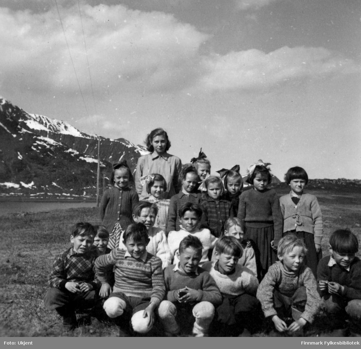 Et gruppebilde av 1. og 2. klasse ved Nuvsvåg skole 1954. Bakerste rad fra venstre: Irene Martinsen og Brynhild Martinsen. Raden foran dem fra venstre: Elbjørg Jensen, Jorunn Karlsen, Berit Mortensen, Marie Karlsen, Grethe Kvivesen, Karin Andersen og Beathe Abrahamsen. De fire neste guttene på raden foran dem fra venstre er: Knut Mortensen (nesten gjemt bak gutten foran ham), Kristian Jensen, Harry Karlsen og Sigmund Olsen. Første rad fra venstre: Jermund Amundsen, Svein Karlsen, Einar Fjellheim, Halvdan Olsen, Leif Karlsen og Herman Andersen. Barna har på seg gensere og skjorter. Jentene har på seg skjørt og de fleste har hårsløyfe. Guttene har på seg bukser og man kan se skoene til enkelte i første rad. Bak gruppen kan man se fjell og strømlinjer.