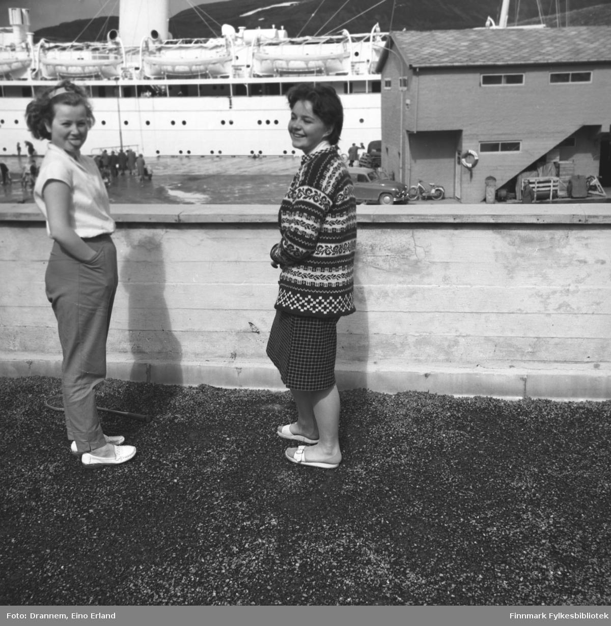 To jenter på verandataket til Tollboden i Hammerfest. De er fra venstre: Turid Karikoski og Maija, etternavn ukjent. Overbygget på et passasjerskip som ligger ved Dampskipskaia ses i overkant av bildet.