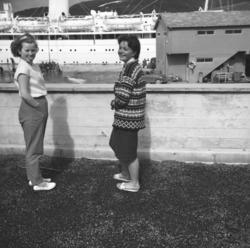 To jenter på verandataket til Tollboden i Hammerfest. De er