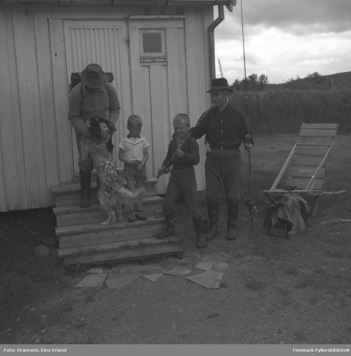 Fire personer og en hund står utenfor en bygning, muligens i Neiden. Gutten i hvit t-skjorte er Hans Gabrielsen, ved siden av er Ole Gabrielsen og mannen til høyre på bildet er Odd Gabrielsen. Mannen med hunden Rexi foran seg er ukjent.