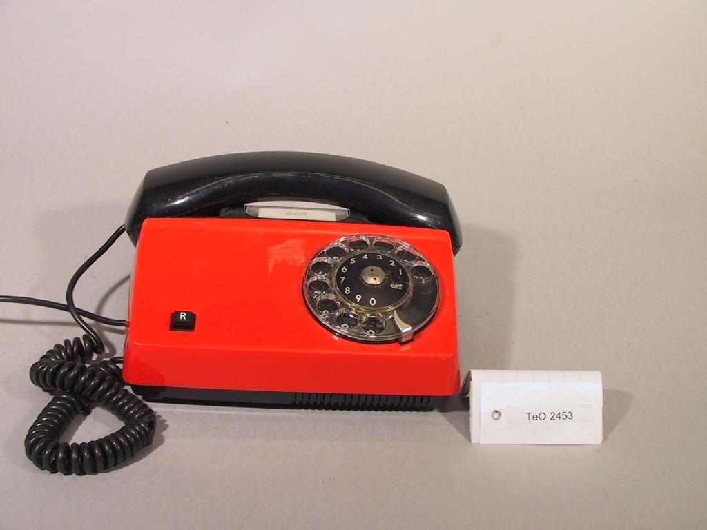 Telefonapparater Diavox 2 st, tillverkade år 1980, för AT-system, huvudapparat, anknytningsapparat till abonnentväxel och sidoapparat. Bordsmodell av plast med röd kåpa, svart mikrotelefon, fingerskiva, R-knapp för aktivering av tilläggstjänster under pågående samtal, högohmig reglerbar ringklocka, elektretmikrofon och elektronisk talkrets med automatisk dämpningskompensering.