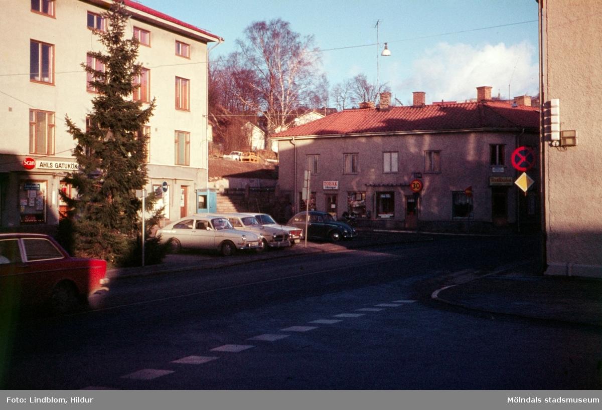 Gamla Torget i Mölndal, 1970-tal. Till vänster ses Kvarnbygatan 43 och till höger Kvarnbygatan 45. En gran är placerad på torget där även bilar står parkerade.  För mer information om bilden se under tilläggsinformation.