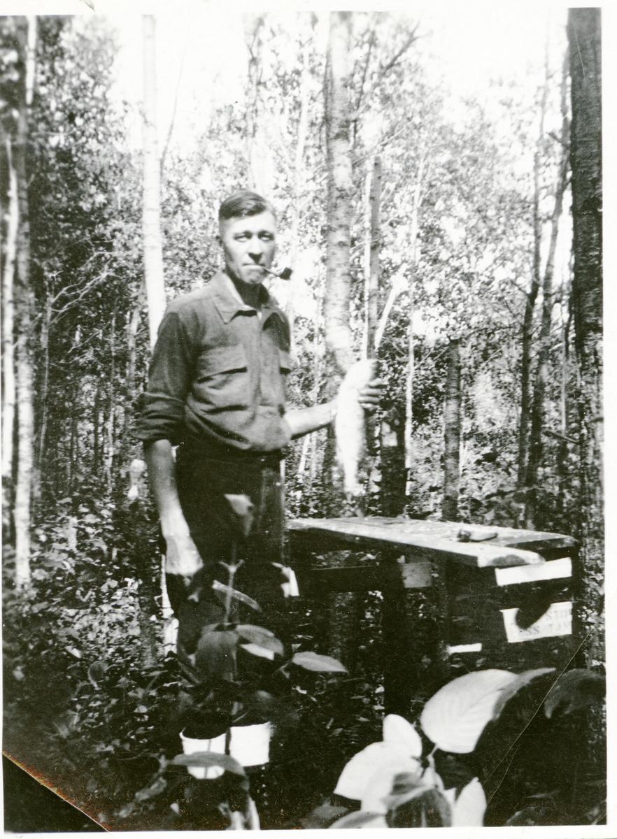 Burt Knatvold renser fisk i skogen.