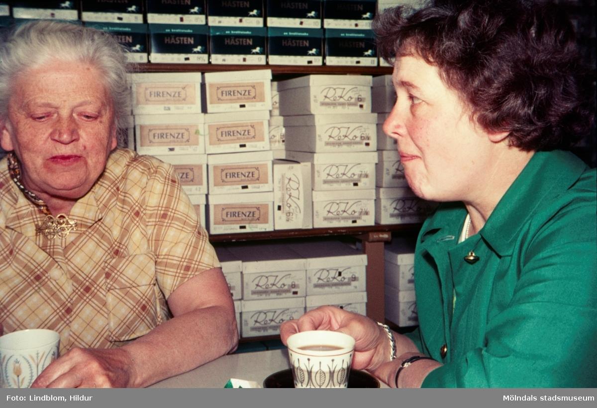 Två kvinnor sitter och fikar i Rasmussons skoaffär med adress Kvarnbygatan 4 vid Gamla Torget i Mölndal, 1970-tal. Till vänster ses tant Karin, d.v.s. Karin Gren, ägare av skoaffären, till höger Märta Sjöberg.  För mer information om bilden se under tilläggsinformation.