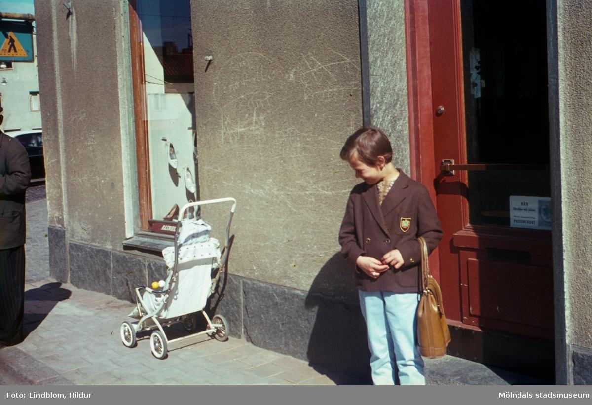 Lisbeth Sjöberg, dotter till Märta Sjöberg, fotograferad på trottoaren utanför Rasmussons skoaffär med adress Kvarnbygatan 4 vid Gamla Torget i Mölndal, ca 1961-1962. På trottoaren står även en sulky.  För mer information om bilden se under tilläggsinformation.