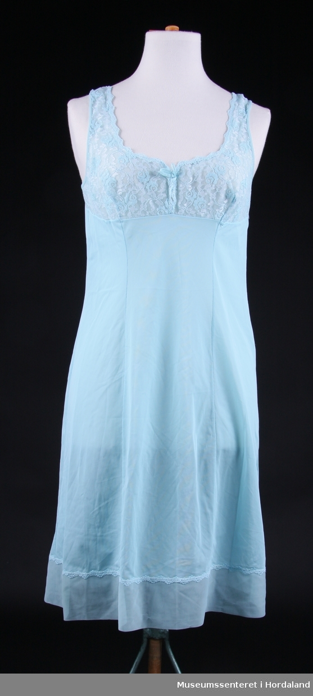 Form: underkjole til ei middels lang kjole, nokså breie stroppar, blondeinnfelling på brystet og blondekant nedst