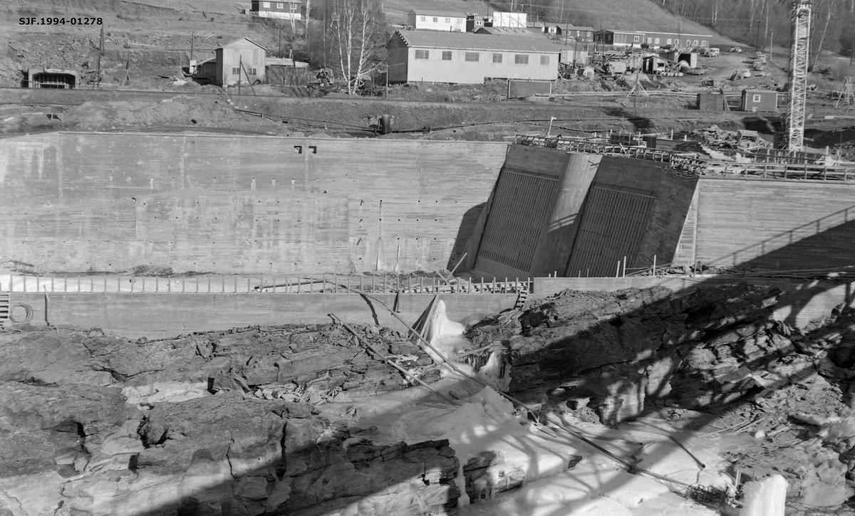 Anleggsområde i forbindelse med bygginga av et kraftverk ved Harpefoss i Gudbransdalslågen.  Dette fotografiet er tatt ved dem som skulle bli «dammen» kraftverksmagasinet med høye murer av armert betong.  Denne dammen ligger ved garden Solbrå, like nord for det trange elvegjelet med fossefall som her ble regulert til fordel for samfunnets energibehov.  Kraftverket utnytter et fall på 34 meter i Gudbrandsdalslågen.  Det ble satt i drift i 1965.  Kraftstasjonen ved Harpefossen har to kaplanturbiner og en årsproduksjon på 427 GWh.