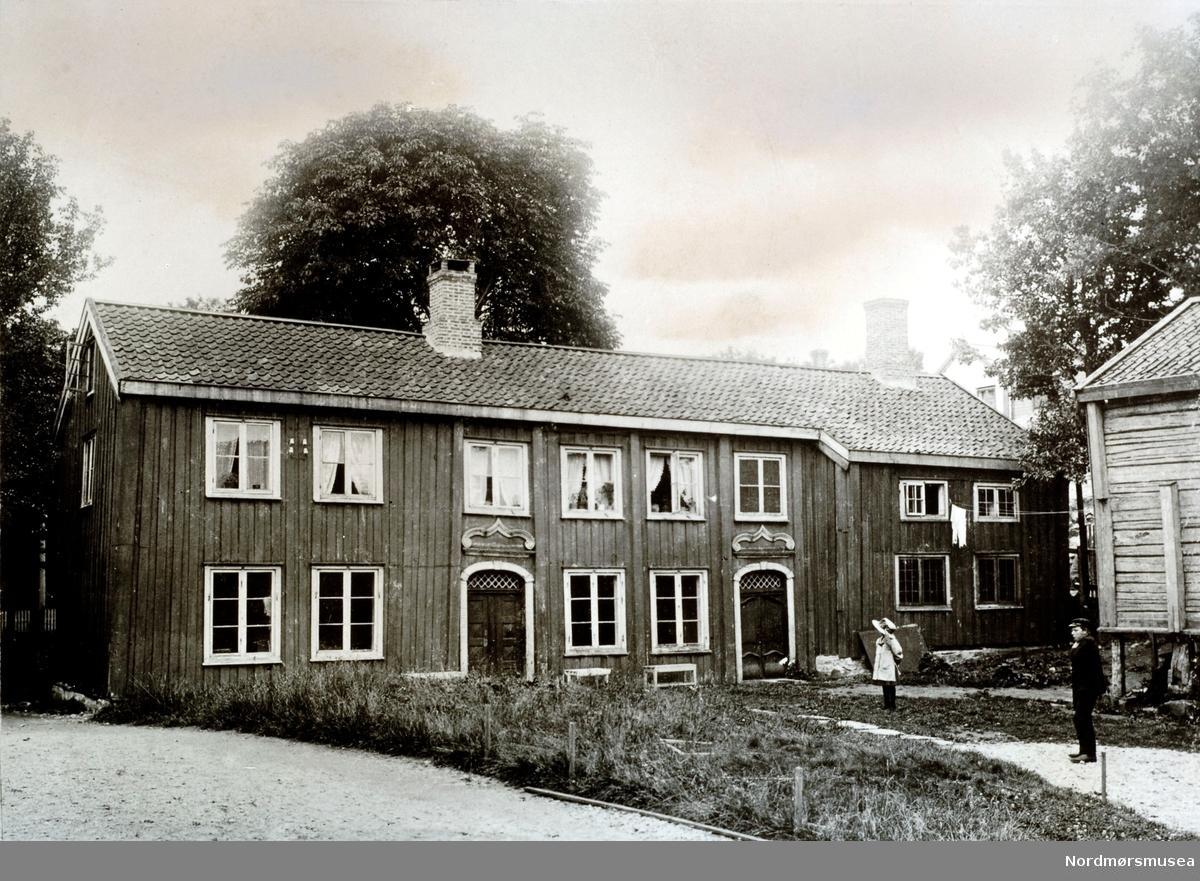 Den gamle Fosna gård. Se tekst i foto  KMb-1982-024.0004. Hovedbygningen på Fosna gård, seinedre overtatt av kommunen/havna/sosialvesen/utdeling av melk/daghjem. Fra tunet på Fosna gård i Vågen. Våningshuset står parallelt med strandlinjen, med stabburet like ved.  (Fra Nordmøre Museum sin fotosamling.)