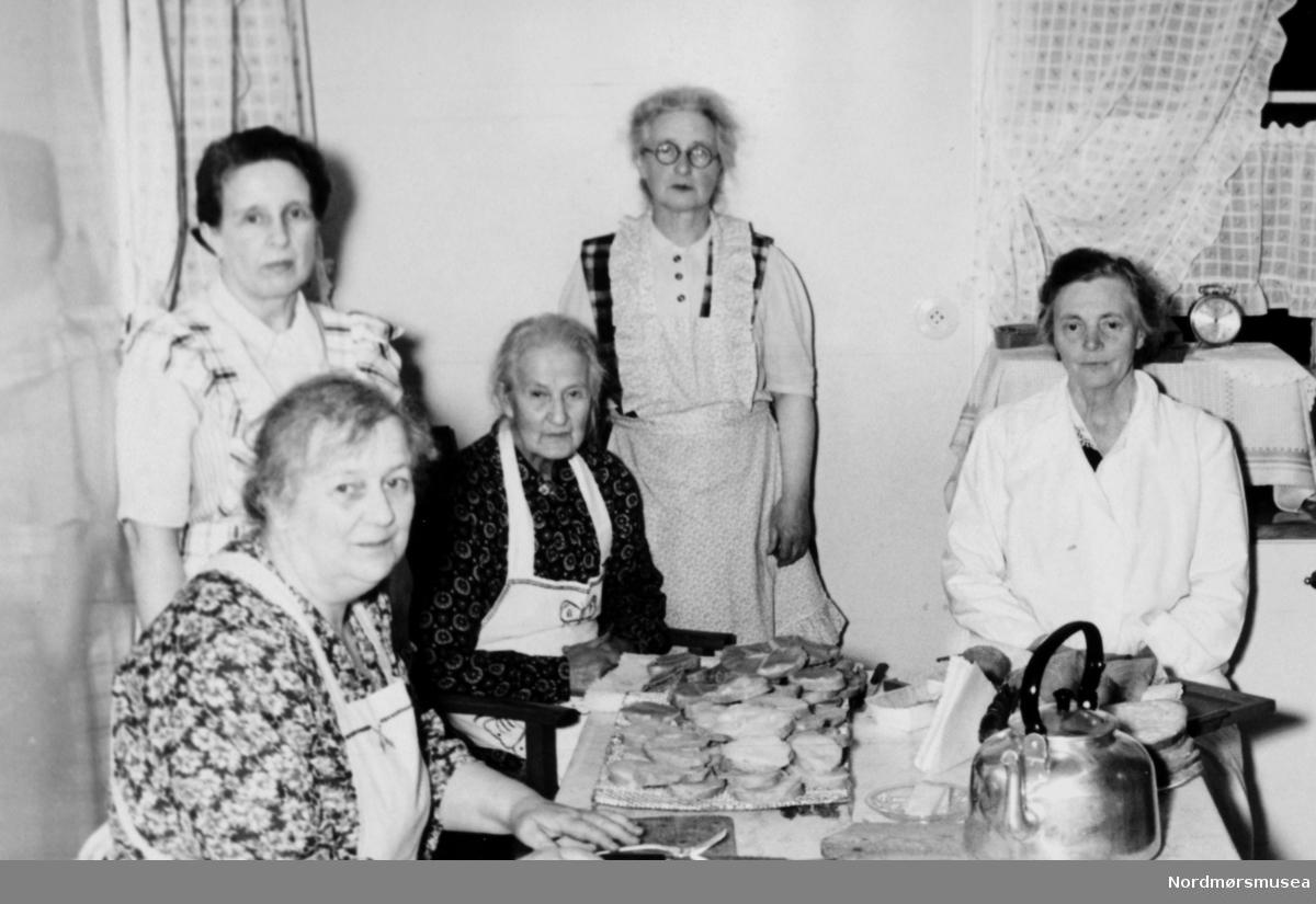 """Kokkelaget"", her sittende ved kjøkkenbordet. Følgende personer er på bildet. 1. rad, sittende ved bordet: Teoline Andersen,  (?) Andersen og Dorthea Myklebost. 2. rad bak: Anna Andersen og (?) Andersen. Fotoet er fra Vågens guttekorps jubileumsmøte hjemme hos Alfred Andersen den 18. oktober 1956. Fra Nordmøre Museums fotosamlinger."