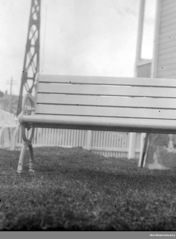 Bildet viser støpejernsføtter på en trebenk, støpt på J. Storviks Mek. Verksted. Benken er plassert utenfor huset til familien Ole Storvik, senere datteren Karen Storvik, senere familien Schamaun, like utenfor verkstedporten. Verkstedet laget nesten alt av støpte gjenstander til alle formål i tidligere tider. Tekst av Peter Storvik. Fra Nordmøre museums fotosamlinger.