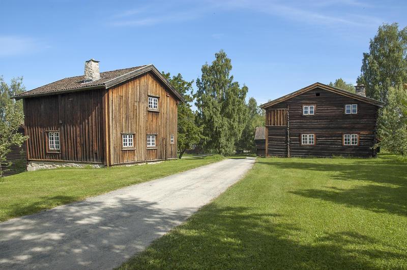 Grusveg som leder inn mellom to brunlige tømmerhus i to etasjer.