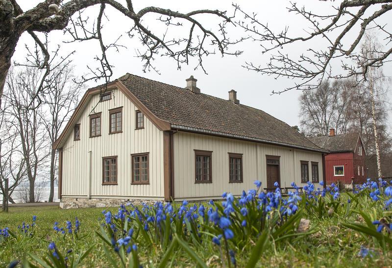 Hvitt hus med valmet tak og blå blomster i forgrunnen.