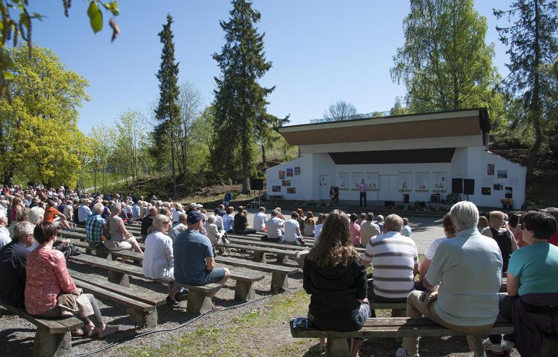 Friluftsscene med artister på og trebenker fylt med publikum