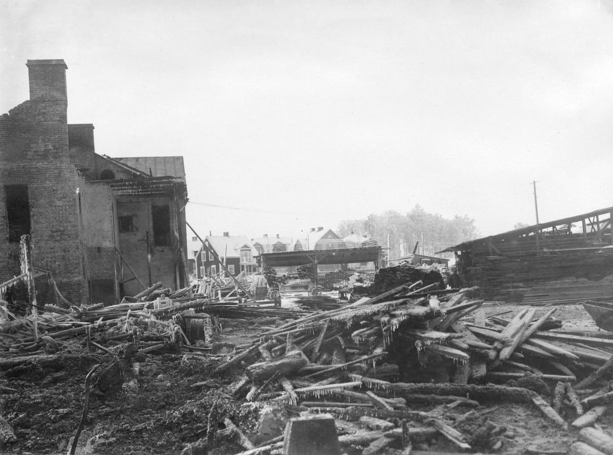 En serie bilder med anknytning till Karlstads Brandkår. Eldhärjad industribyggnad på Tormestad år 1927. I bakgrunden syns villor på Herrhagen.