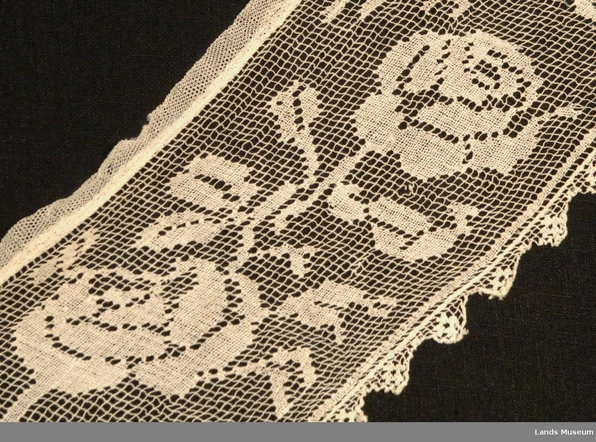 Kjolekrage med filert rosemønster. Påsydd linning av tyll mot halsen for feste på kjolen. Kragen ender i lange spisser.
