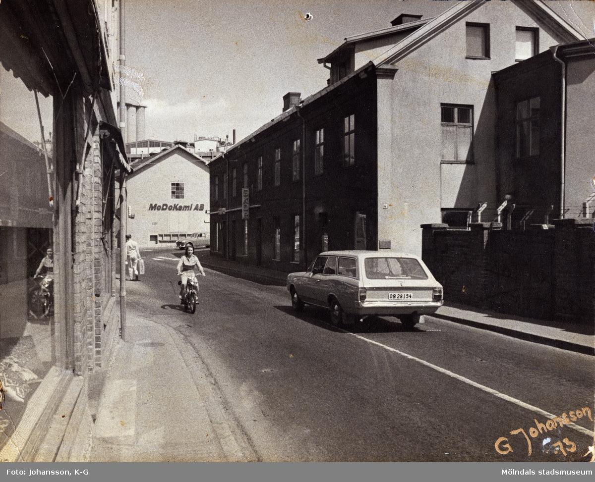 Kvarnbygatan i riktning mot Gamla Torget i Mölndal, år 1973. Till vänster ses huset Kvarnbygatan 37, i mitten nr 6 (MoDo Kemi AB) och till höger nr 4, Rasmussons skoaffär.