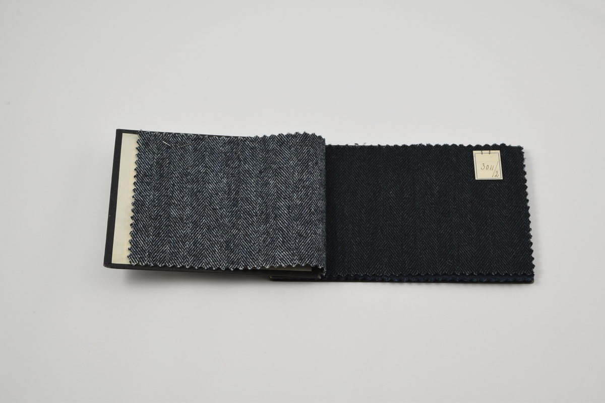 Prøvebok med 4 prøver. Middels tykke ullstoff med fiskebensmønster. Alle stoffer er merket med en firkantet papirlapp festet med metallstifter hvor nummer er påskrevet for hånd.   Stoff nr. 3011/1 (blå), 3011/2 (gråblå), 3011/3 (blå), 3011/4 (fiolett).