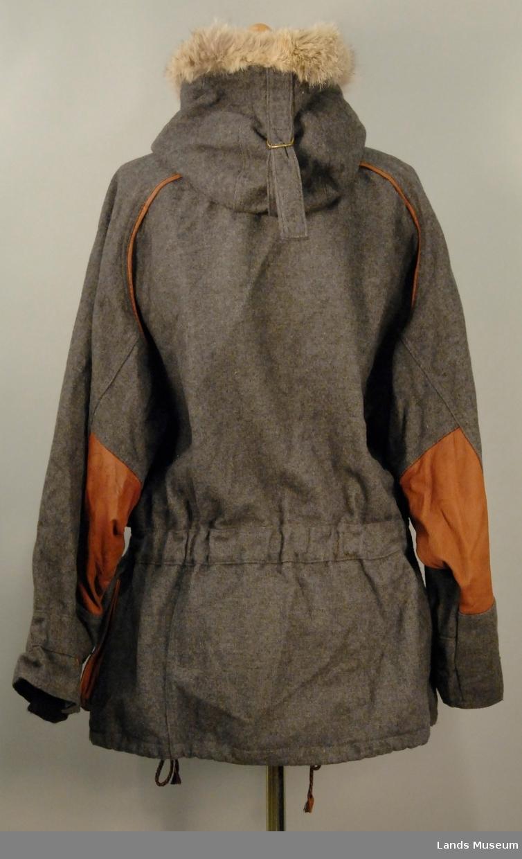 """Jakke og nikkers i grå ull med detaljer i skinn. Dressen vart brukt under OL i Albertville 1992 som representasjon for LOOC (Lillehammer Olympiske Organisasjonskomitée). Fóret er i to blåfarger i krystallmønsteret som var ein del av LOOCs designprogram. Logo for Lillehammer 1994 på alle knapper og i skinn på lomme. Brodert """"mann med fakkel"""" foran på jakka. Skinndetaljer på lommer, biser rundt erme, på albue og på kne, og rundt knapper. Ermeopplegg i svart. Hette med avtakbar pelskant."""