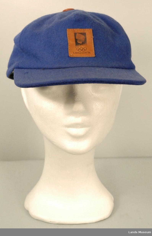 """Caps i blå ull med brune skinndetaljer. Logo for OL Lillehammer 1994 i skinn midt foran. Nedbrettbar """"øreklaffer"""", som går heilt rundt bak. Skinnknapp på toppen."""