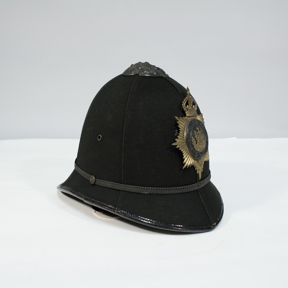 """Britiskinspirert hjelmform """"Bobby typen"""". Foran er Oslos byvåpen omringet av belte og stjerne, med krone over. På toppen er en rose av metall."""