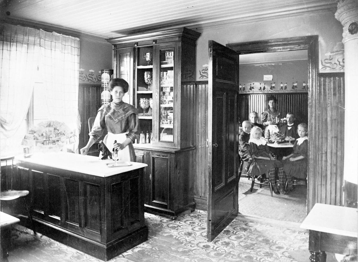Interiör från Wilanders Café i Rödboharen, Norrsundet.  Familjen Wilander, Jöns och Sofia med barnen Karl Gustaf, Anna Sofia och Astrid Elisabet sitter vid kaffebordet.