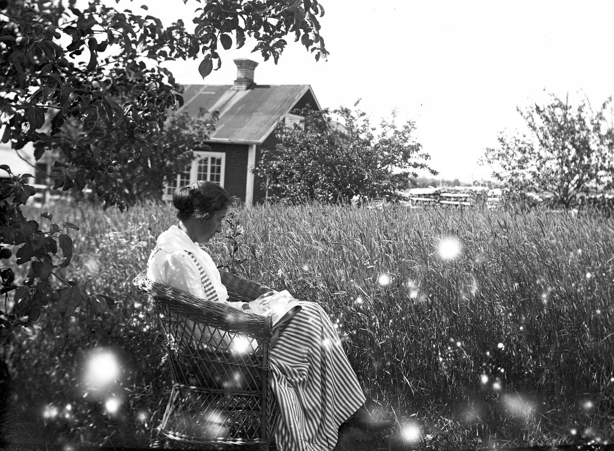 Sitter och läser. Tidsomfånget är 1900 - 1940