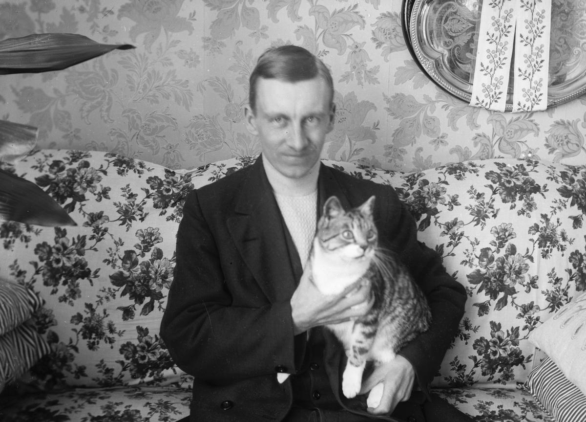 Man med katt. Tidsomfånget är 1900 - 1940