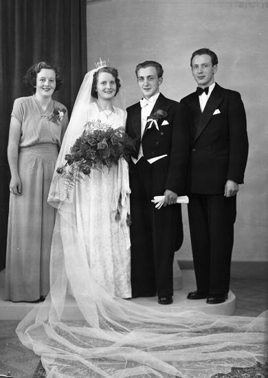 ca202bc995b6 Foto av ett brudpar med bröllopsvittnen. Bruden är klädd i vit, mönstrad  brudklänning med slöja och brudkrona. Brudgummen bär frack. Helfigur.  Ateljéfoto.