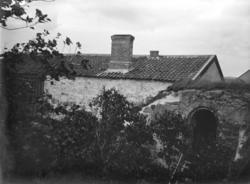 Foto av en magasinsliknande stenbyggnad. Till höger syns en