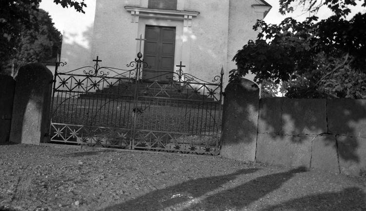Foto på en kyrka med en stenmur och en grind utanför.