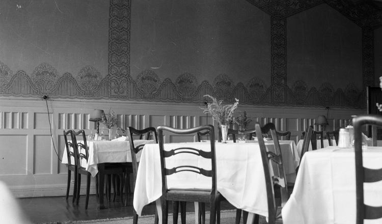 En sal med ett antal dukade bord, med lampor och blommor, och stolar. Interiör Industri-restaurangen Kristianstad 1943