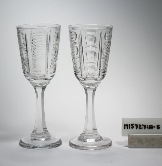 Vinglas/servisglas. Konoid kupa, sexkantigt ben, skivfot. På kupan vertikala band av oliver och skär. Ofärgat klarglas. Inskrivet i huvudkatalogen 1954. Funktion: Vinglas